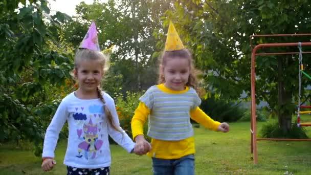 Dvě hezká malá dívky drželi se za ruce a hraje na čerstvém vzduchu