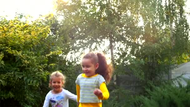 Two happy pretty little girls holding hands and playing in the fresh air.