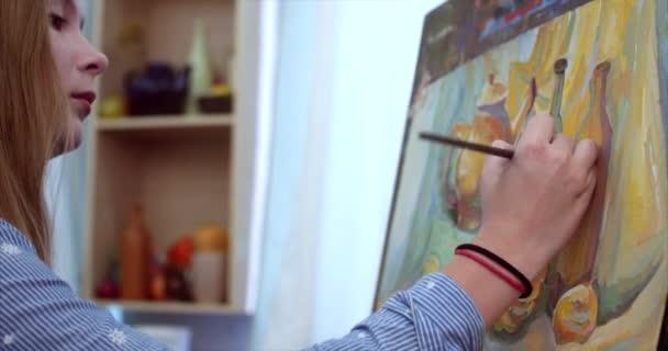 Una giovane bella Female Artist è un Art Studio, seduto dietro un cavalletto e pittura su tela. Processo di disegno: nello Studio darte di artisti mano Art ragazza con una pittura a pennello su Canvas.4k