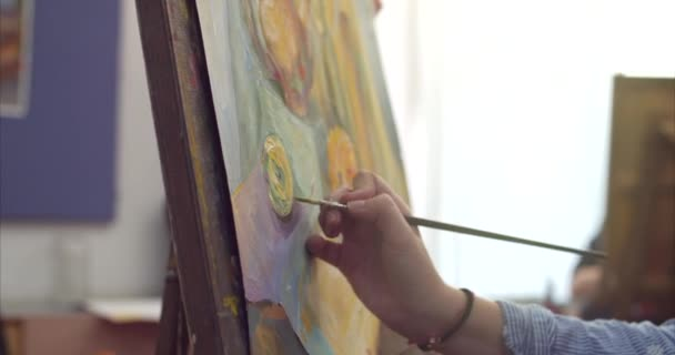 A Young Beautiful Female Artist is in an Art Studio, Sitting Behind an Easel and Painting on Canvas. Drawing Process: in the Art Studio of the Artists Hand Art Girl with a Brush Painting on Canvas.4K
