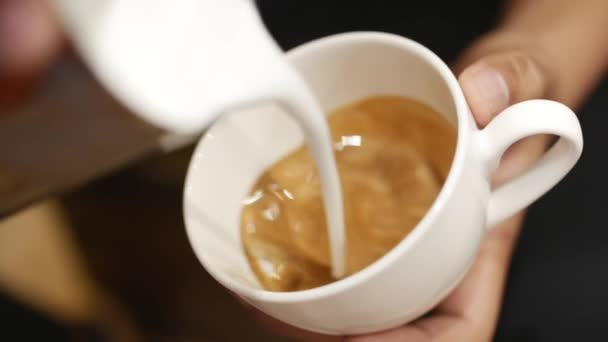 Pouring stream milk into a cup of espresso, slow motion. Close-Up. Stock footage.