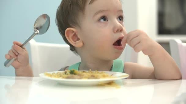 Malé dítě sedí u stolu v bryndáček a jíst vlastní špagety, dítě jí ochotně.