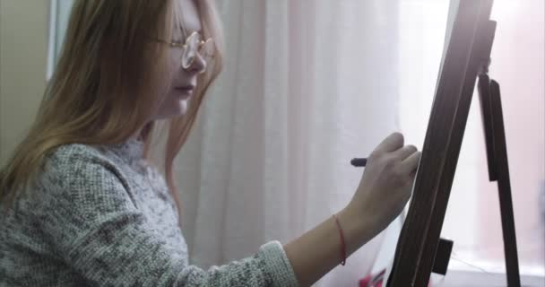 Young Beautiful Female Artist is in an Art Studio, Sitting Behind an Easel and Painting on Canvas. Drawing Process: in the Art Studio of the Artists Hand Art Girl with a Brush Painting on Canvas.4K