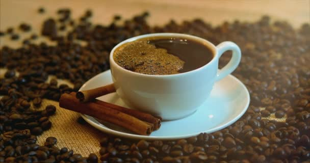 Coffee cup and coffee beans. A white cup of evaporating coffee on the table with roasted bean. Stock footage. 4K