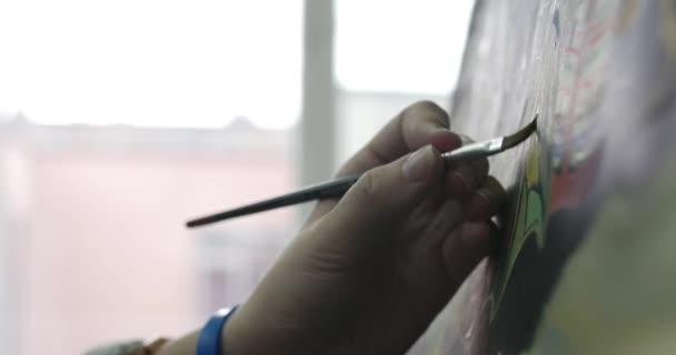Giovane bella donna artista è un Art Studio, seduto dietro un cavalletto e pittura su tela. Processo di disegno: nello Studio darte di artisti mano Art ragazza con una pittura a pennello su Canvas.4k