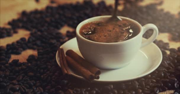 Šálek kávy a kávových zrn. Bílý hrnek odpařovací kávu na stůl s pražených bobů. Stopáže 4k.