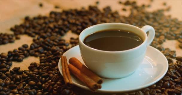 Csésze kávé- és babkávé. Egy fehér kupa párolgó kávé az asztalra és sült bab. Stock footage 4k.