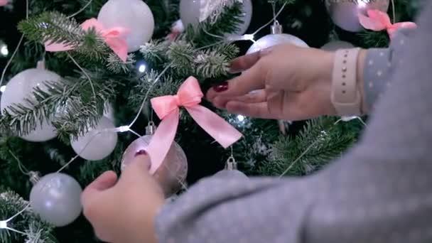 Rukou mladé ženy šíření luk na vánoční stromeček, vyzdobit sváteční vánoční stromeček s slavnostní osvětlení a vánoční koule
