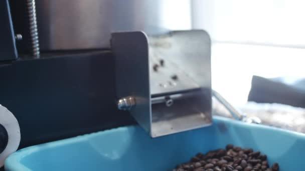Šálek kávy a kávových zrn. Bílý hrnek odpařovací kávu na stůl s pražených bobů. Slow Motion káva pour