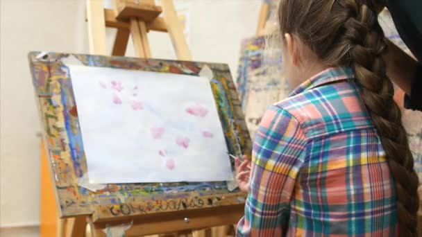 Young Pretty Artist is in the art Studio, Sitting at the Easel and Draws on Canvas, Asks the Mentor how to Draw. Drawing process: in the art Studio Girl Wth a Brush Painting on Canvas.