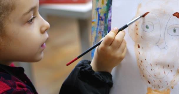 Giovane artista femminile carina è un Art Studio, seduto dietro un cavalletto e pittura su tela. Processo di disegno: nello Studio darte di artisti mano Art ragazza con una spazzola la pittura su tela.