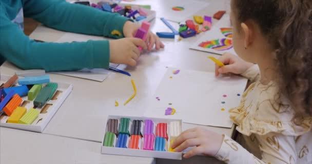 Roztomilé malé děti sedí u stolu modeluje různé postavy z vyrobené z barevných modelování Plastelíny v dětském pokoji. Vývoj umění modelování u dětí.