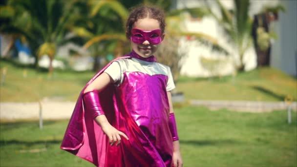 Gyönyörű kislány egy szuperhős jelmez, öltözött egy köpenyt, és maszk egy hős, keresi a kamerát. A boldog gyermekkor fogalma.