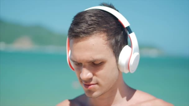 Clouse Up Handsome Young Man Listening Music from his Smartphone in Wireless White Headphones, Dancing on Beach at Background Blue Sky.