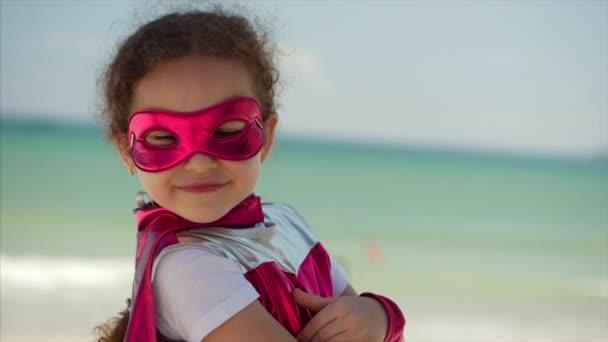 Gyönyörű kislány a szuperhős jelmez, öltözött a Pink Cloak és a maszk a hős. Játszik a háttérben tenger és a kék ég és a felhők, küld egy ökle előre. Fogalmának a Happy