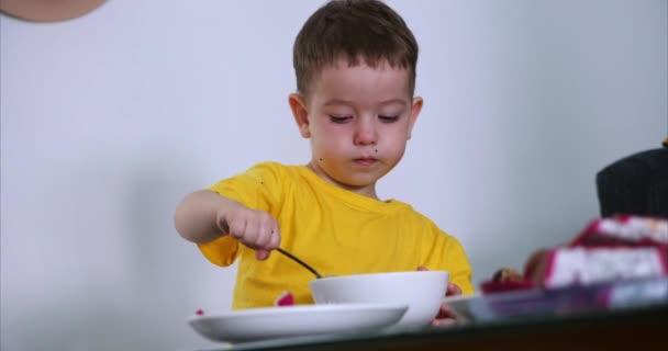 Kis aranyos gyermek ül az asztalnál, és megeszi a saját zabpehely, és megeszi egzotikus gyümölcsök, a Baby megeszi willingly. A koncepció egy boldog gyermekkori.