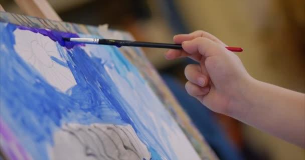 Giovani mani dellartista, piccola donna artista dipinge una tela con pennello, seduto un tavolo e disegnare su tela. Processo di disegno: in artisti arte studio mano baby girl schizzi su Canvas. Shot primo piano