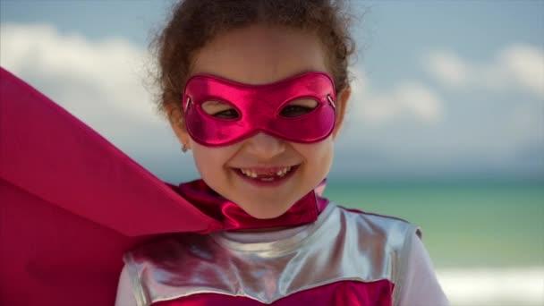 Portré aranyos kislány a szuperhős jelmez, öltözött a Pink Cloak és a maszk a hős. Játszik a háttérben tenger és a Blue Sky és a felhők. A boldog gyermekkor fogalma.