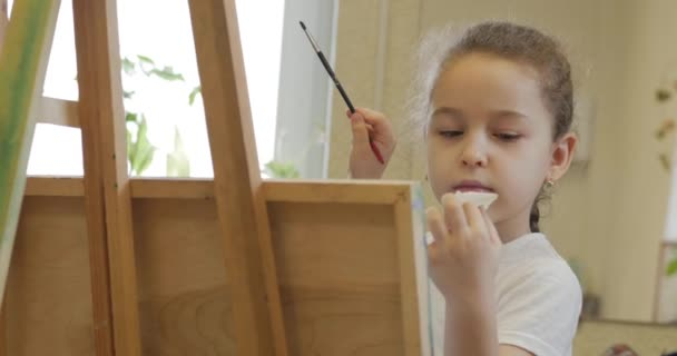 Young Hands of the Artist, Little Woman Artist Paints a Canvas with Brush,Sitting a Table and Draw on Canvas. Process of Drawing: in Artists Art Studio Hand Baby Girl Sketching on Canvas.Shot Closeup