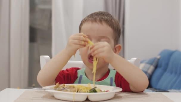 Ein kleines Kind sitzt in einem Lätzchen an einem Tisch und isst seine eigenen Spaghetti, das süße Baby isst bereitwillig. niedliches kleines Baby, das ihr Abendessen isst. 4k