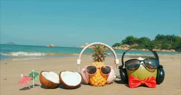 Egy trópusi tengerpart közeli gyümölcs napszemüveg a forró nyári nap mentén a trópusi parton, ananász és kókusz a fejhallgató az Ocean background. A trópusi nyári Patty koncepció.