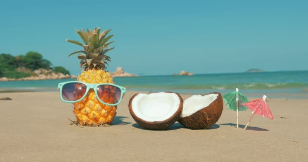 On a Tropical Beach Close-Up of Fruit in Sunglasses Under the Hot Summer Sun Along the Tropical Exotic Coast, Pineapple in Sunglasses on the Ocean Background. Concept Topical, Summer, Party, Holiday.
