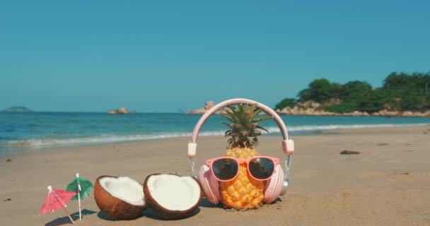 Na tropické pláži blízko plodů v paprskových skleničkách pod horkým letním sluncem po tropické exotickém pobřeží, ananasu a ve sluchátkách na pozadí oceánu. Koncept tropického letního svátku
