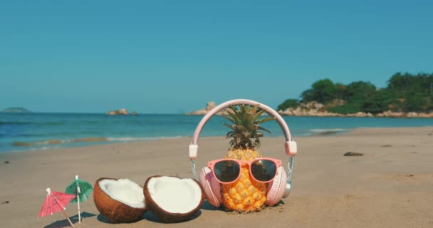 On a Tropical Beach Close-Up of Fruit in Sunglasses Under the Hot Summer Sun Along the Tropical Exotic Coast, Pineapple and in Headphones on the Ocean Background. Concept of a Tropical Summer Holiday