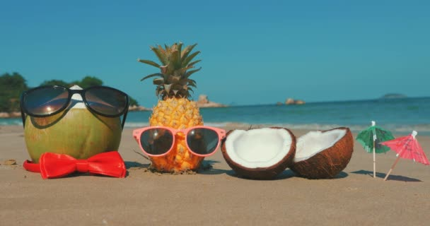 On a Tropical Beach Close-Up of Fruit in Sunglasses Under the Hot Summer Sun Along the Tropical Coast, Pineapple and Coconut in Headphones on the Ocean Background. Concept of a Tropical Summer Party.