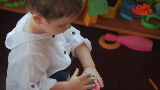 Roztomilé malé dítě si hraje s hračkama v hračkářství. Koncepce šťastné dětství.