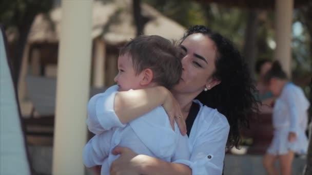 Šťastná matka hubuje své dítě na pobřeží. Roztomilý kluk líbá svou mámu a něžně Hugse. Koncepce Mami s dítětem venku, šťastná rodinka, šťastné dětství, děťátko.