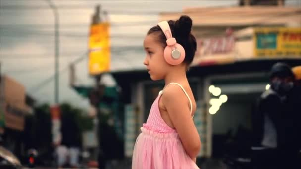 Portrait of a Cute Child Standing By the Road, a Wonderful Little Cute Girl in a Pink Dress and Pink Headphones Looking Away, Against the Background of Passing Cars and Motorcycles.