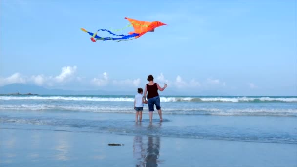 Happy grandmother with child the playing flying kite, the family runs on the sand of a tropical ocean playing with the older kite. Concept Happy and carefree childhood.