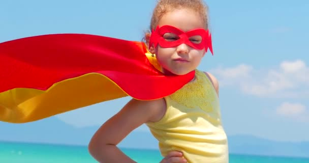Close Up Portrait Beautiful Little Girl in the Superhero Costume, Dressed in a Red Cloak and the Mask of the Hero. Plays on the Background Sea and Blue Sky and Clouds. Concept of a Happy Childhood.