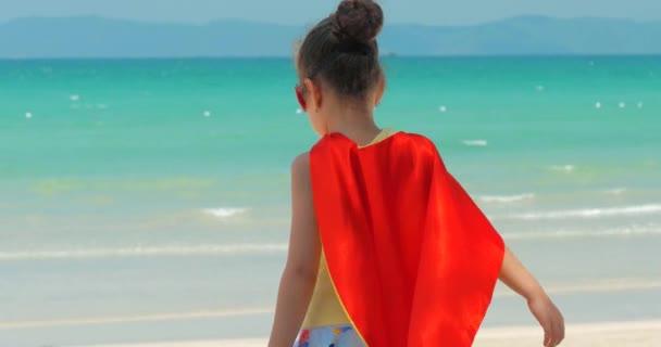 Aranyos kislány a szuperhős jelmez, öltözött a Red Cloak és a maszk a hős. Játszik a háttérben tenger és a Blue Sky és a felhők. A Happy chilhood koncepciója.
