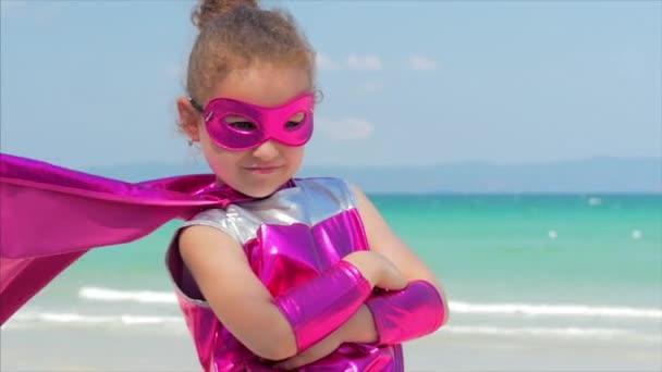 Bella bambina in costume da supereroe, vestita con un mantello rosso e la maschera delleroe. Gioca sul mare di sfondo e cielo blu e nuvole, invia un pugno in avanti. Concetto di unelartà felice.