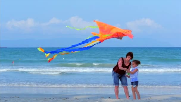 Happy grandmother with child the playing flying kite, the family runs on the sand of a tropical ocean playing with the older kite. Concept Happy and carefree childhood. Soft Focus