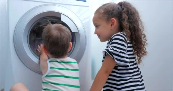 Cute Children Looks Inside the Washing Machine. Cylinder Spinning Machine. Concept Laundry Washing Machine, Industry Laundry Service.
