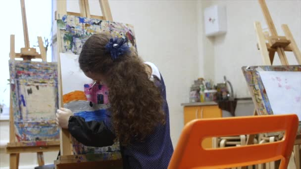 Young cute Female Artist is in an Art Studio, Sitting Behind an Easel and Painting on Canvas. Drawing Process: in the Art Studio of the Artists Hand Art Girl with a Brush Painting on Canvas.
