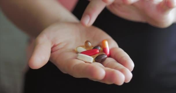 In Großaufnahme weiblicher Hände schüttet jemand ein Bündel verschreibungspflichtiger Opiattabletten in die Hand. Gesundheitskonzept, Medikamente, Verhütung.