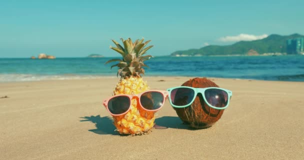 On a Tropical Beach Close-Up of Fruit in Sunglasses Under the Hot Summer Sun Along the Tropical Exotic Coast, Pineapple and Coconut in Sunglasses on the Ocean Background.Concept Topical Summer Holiday