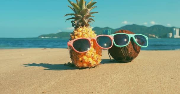 Egy trópusi tengerpart közeli gyümölcs napszemüveg a forró nyári nap mentén a trópusi egzotikus Coast, ananász és kókusz a napszemüveg az óceán háttérben. Concept aktuális nyári szünet