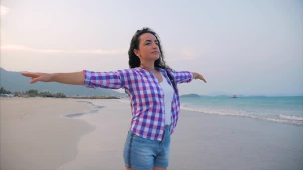 Nő felemelt karokkal egy trópusi strandon Close-up portré európai gyönyörű aranyos barna, fiatal nő vagy vidám lány emelés karok fel ünneplő élet Scenic Landscape, fúj szél Haj a