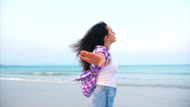 Woman with arms raised On a Tropical Beach Close-Up Portrait of European Beautiful Cute Brunette, Young Woman or Cheerful Girl lifting Arms Up Celebrating Life Scenic Landscape, Blowing Wind Hair the