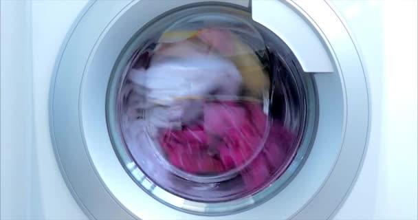 Großaufnahme Industrielle Waschmaschine wäscht farbige Kleidung und weiße Bettwäsche, weiße gestreifte Kleidung. Zylinderspinnmaschine. Konzept Waschmaschine, Industrie Wäscheservice.