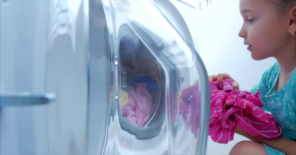 Load clothes to the washing machine. Little Girl Loads the Laundry in the Washing Machine and includes washing. Concept Laundry Washing Machine, Industry Laundry Service.