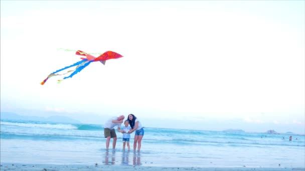 Happy Family With Child Launch a Kite, Mother Father and Daughter Playing with the Older Kite in the Ocean Background in Sunset. Concept of a Happy and Carefree Childhood.