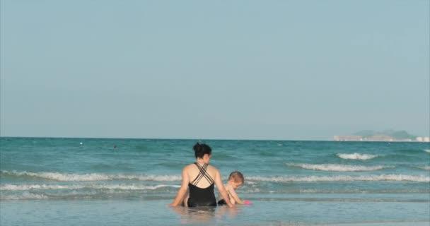 Boldog és gondtalan anya és fia játék a tenger, napozni, úszni. Gyermekek és felnőttek játszanak a tenger egy trópusi strandon. Koncepció boldog család.