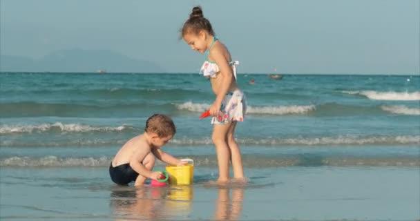 Glückliche und unbeschwerte Kinder, die am Meer mit Sand spielen. Kinder spielen, Geschwister spielen am Meer. Glückliche Kindheit.