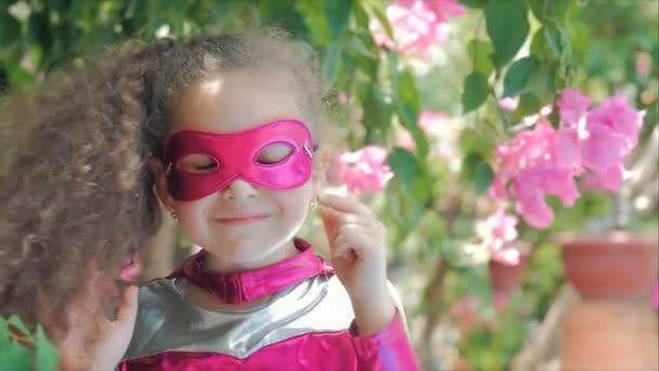 Gyönyörű Llittle Girl a szuperhős jelmez, öltözött a Pink Cloak és a maszk a hős. Játszik a háttérben a tenger és a kék ég és a felhők, korrigálja a Pink Mask arcán